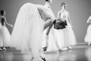 A dancer pauses during rehearsal to make small adjustments to her shoes and costume. The image was taken in June 2014 in Los Angeles while shadowing a dance company during preparations for an upcoming performance.